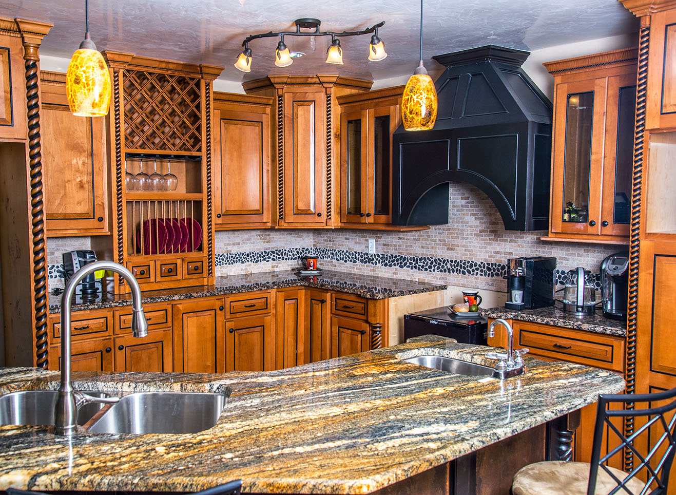 "Large kitchen island counter made of Juperana Fantasy. Baltic Brown Granite makes up the ""L"" counter"