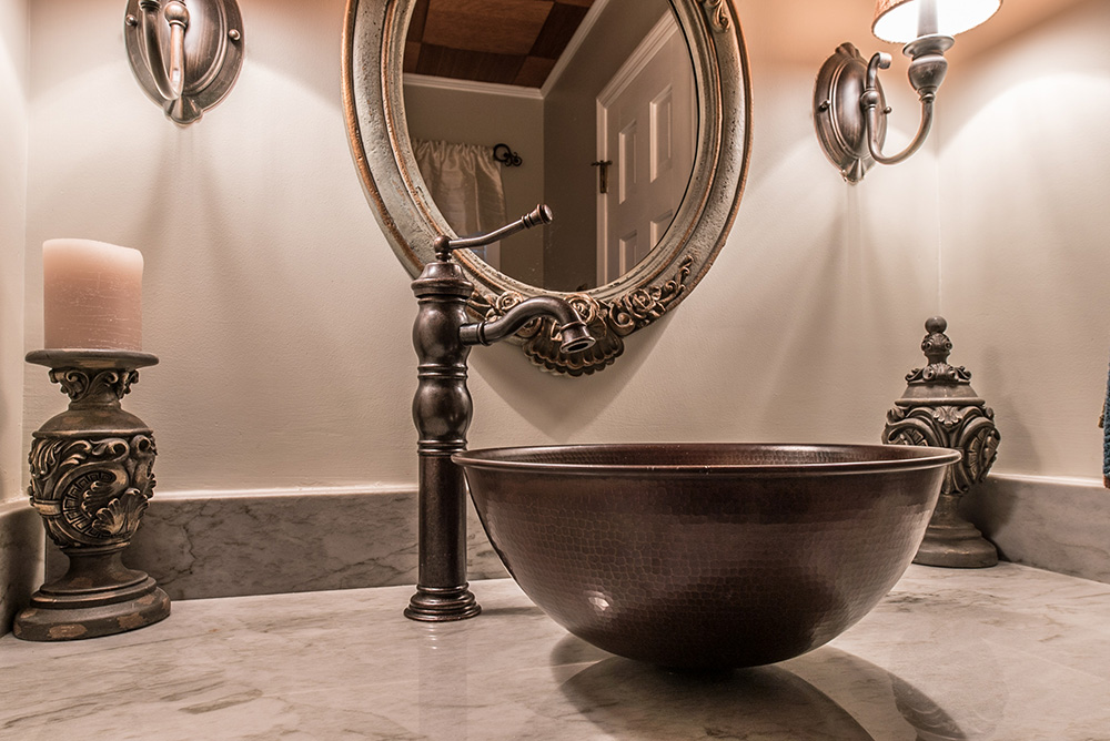 Copper vessel and faucet adding great contrast to the naturally light Sea Pearl quartzite