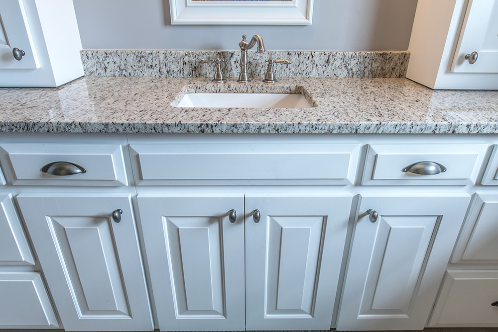Bathroom vanity topped with Verona granite and white shaker style cabinets for the base